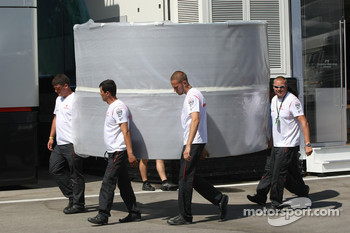 McLaren Mercedes team members carrying part of their motorhome