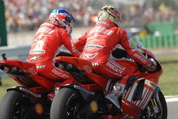 Race winner Casey Stoner is congratulated by Loris Capirossi