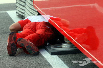 A Ferrari team member rolls under the Hospitality Unit to check something