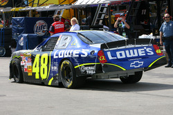Pole sitter Jimmie Johnson takes the battered Lowe's Chevy back to his garage stall after hitting the wall in turn 4