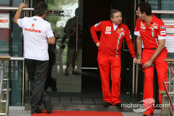 A team member from McLaren Mercedes Walks into the Ferrari building as Jean Todt, Scuderia Ferrari, Ferrari CEO talks outside