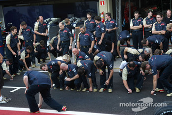 Scuderia Toro Rosso, team members pick up stickers off the floor