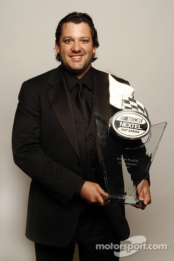 Tony Stewart holds the trophy given to the sixth place driver in the NASCAR NEXTEL Cup Series standings