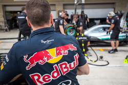 A Red Bull Racing mechanic watches the Mercedes AMG F1 team practice pit stops