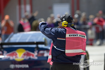 A member of the event staff directs the NASCAR Sprint Series cars to pit road from the garage area