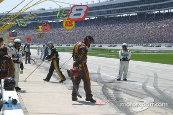 Crews sweep and blow clean the pit lane after pit stops