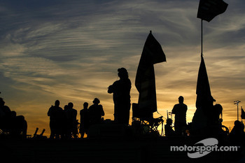 Fans watch the Subway Fresh Fit 500 as darkness falls over Phoenix International Raceway