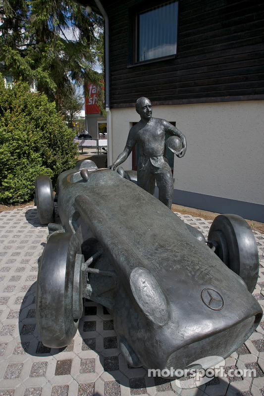 A bronze statue of Juan Manuel Fangio and his Mercedes-Benz W196 at the track entrance