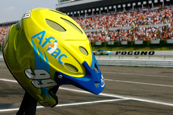 An Aflac crew members helmet rests atop the jack handle as Carl flashes by on the fronstretch