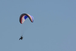 A paraglider flys over the circuit