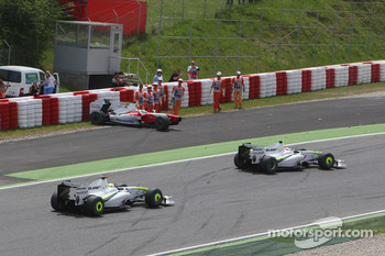 Rubens Barrichello, Brawn GP and Jenson Button, Brawn GP passing the damaged car of Jarno Trulli, Toyota F1 Team