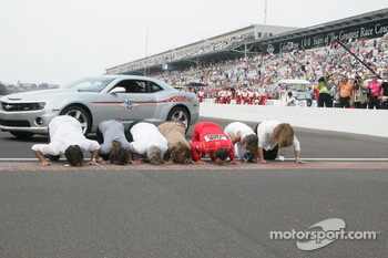 Race winner Helio Castroneves kisses the yard of bricks with friends and family