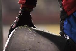 A pit member balances a tire before a pit stop