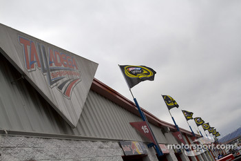 NASCAR Sprint Cup flags fly under cloudy skies and over the garage area