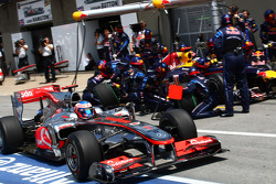 Jenson Button, McLaren Mercedes passes Sebastian Vettel, Red Bull Racing during a pit stop