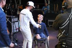 Lewis Hamilton, Mercedes AMG F1 en el escenario con con el piloto de British Formula 4 Billy Monger