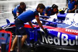 Monteurs duwen de wagen van Pierre Gasly Toro Rosso STR13 Honda in de garage