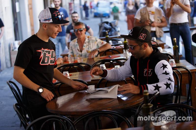 Andrea Migno mit T-Shirt und Cap von Nicky Hayden serviert Espresso für Danilo Petrucci mit Jacke vo