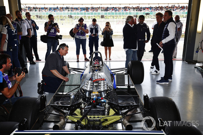 A six-wheeled Williams FW08 is prepped, as Karun Chandhok, Keke Rosberg and Nico Rosberg watch on