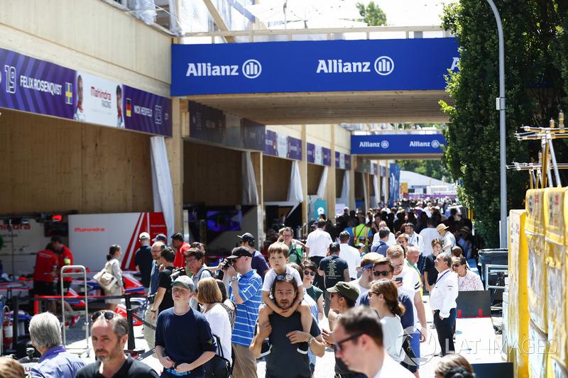 Fans walk the pit lane