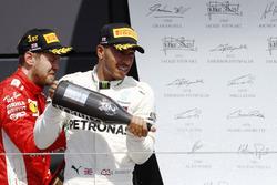 Sebastian Vettel, Ferrari, and Lewis Hamilton, Mercedes AMG F1, celebrate on the podium with champagne