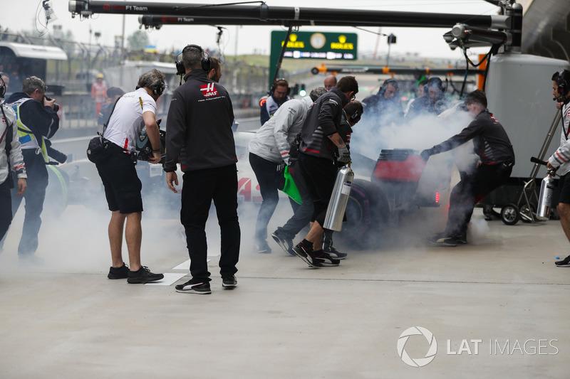The smoking Romain Grosjean Haas F1 Team VF-18 Ferrari is wheeled into the team's garage