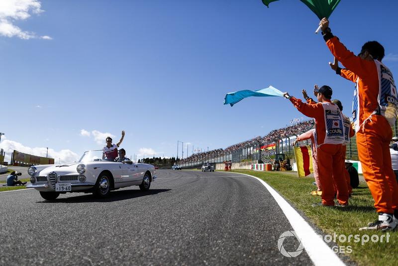 Des commissaires agitent des drapeaux alors que Charles Leclerc, Sauber, passe lors de la parade des pilotes