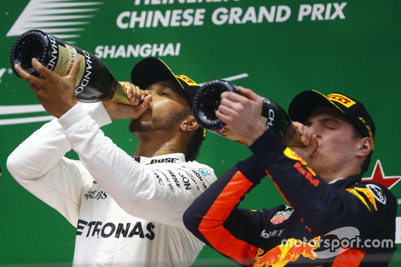 Race winner Lewis Hamilton, Mercedes AMG, and Max Verstappen, Red Bull Racing, celebrate with Champagne on the podium