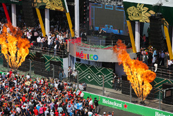 DJ Hardwell plays from the podium after the driver celebrations with flame throwers either side
