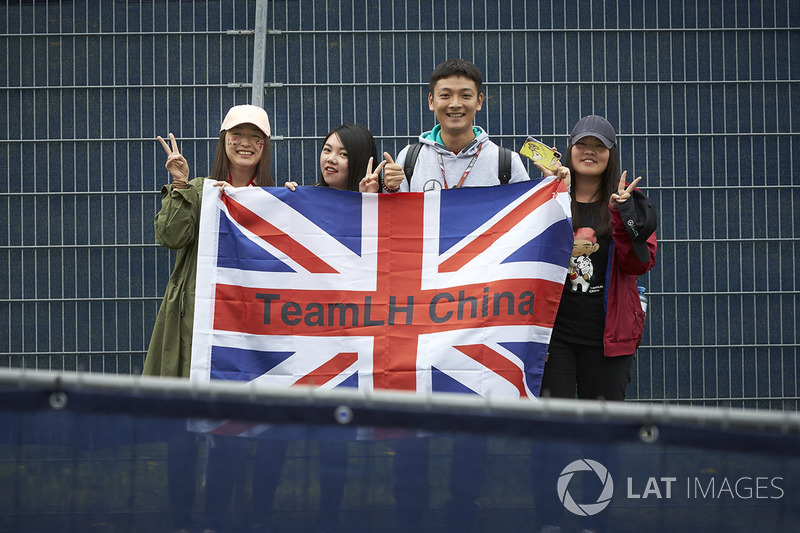Fans of Lewis Hamilton, Mercedes AMG F1 W09, pose with a flag