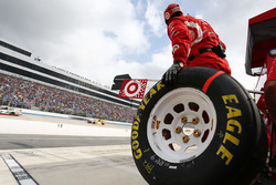 A Chip Ganassi Racing crew member waits for a pit stop with a Goodyear tire