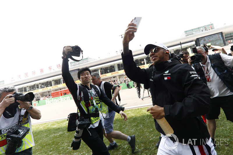 Lewis Hamilton, Mercedes AMG F1, is mobbed by photographers, as he takes a picture of fans with his smart phone