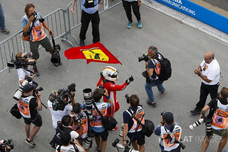 Sebastian Vettel, Ferrari, celebrates victory by waving a Prancing Horse flag