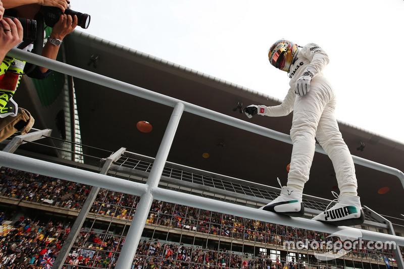 Lewis Hamilton, Mercedes AMG, climbs a fence to celebrate pole position