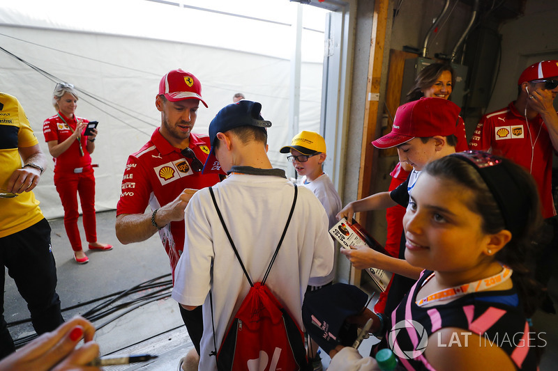 Sebastian Vettel, Ferrari, signs autographs for grid kids