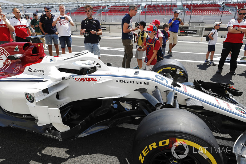 Dei tifosi fotografano la monoposto di Marcus Ericsson Sauber C37, sotto la supervisione dei membri del team Sauber