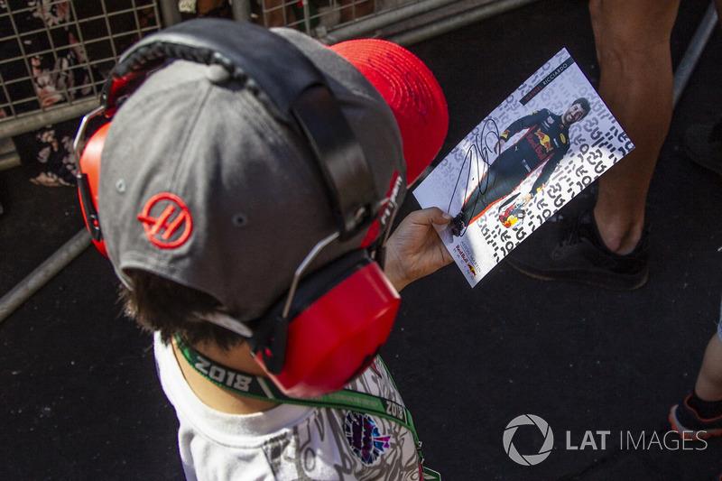 Un giovane tifoso con una cartolina autografata da Daniel Ricciardo, Red Bull Racing