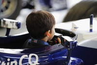 A young fan gets behind the wheel