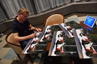 Mika Hakkinen signs his photos from 1993 Australian GP