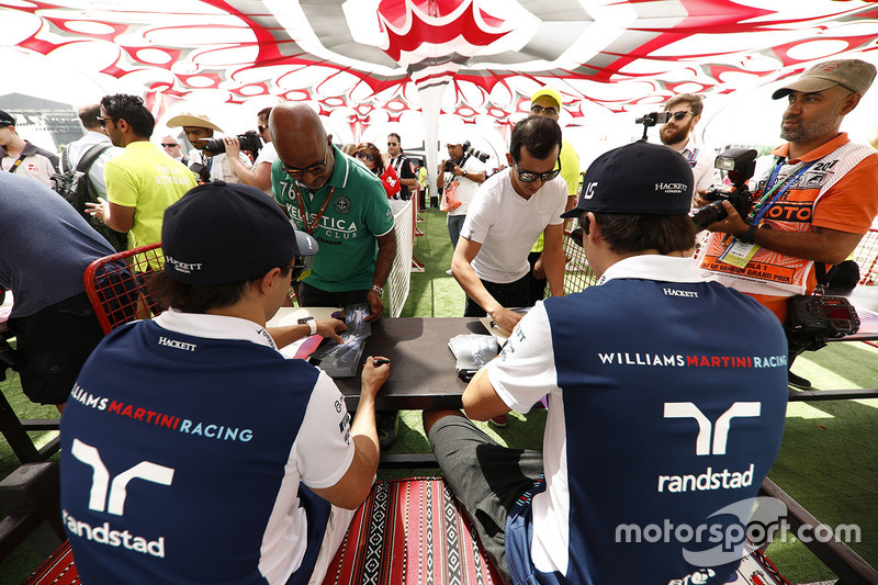 Felipe Massa, Williams, and Lance Stroll, Williams, sign autographs for fans