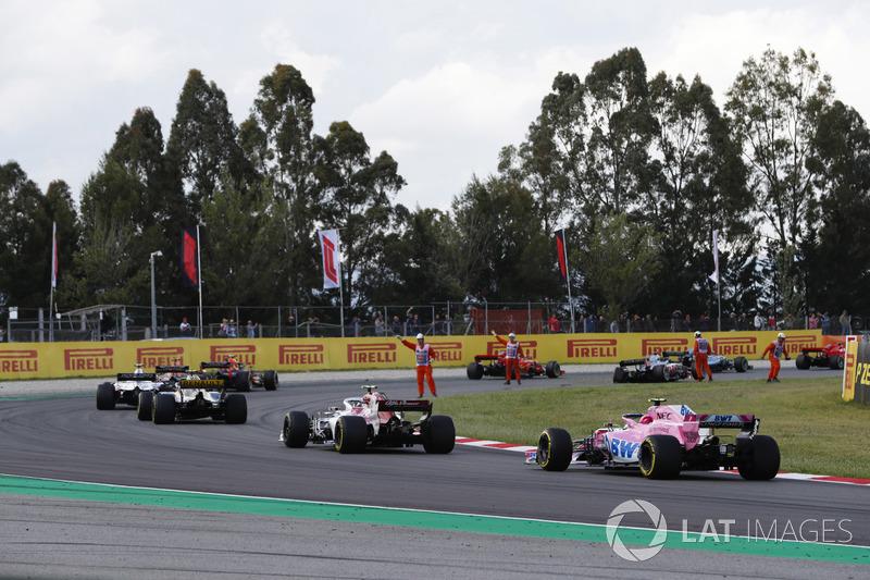 I marshal indicano ai piloti, inclusi Esteban Ocon, Force India VJM11 ed Esteban Ocon, Force India VJM11, la zona con i detriti lasciati dall'incidente nel giro di apertura