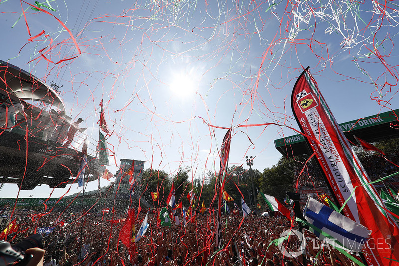 Streamers fall as the top three drivers celebrate on the podium, Champagne