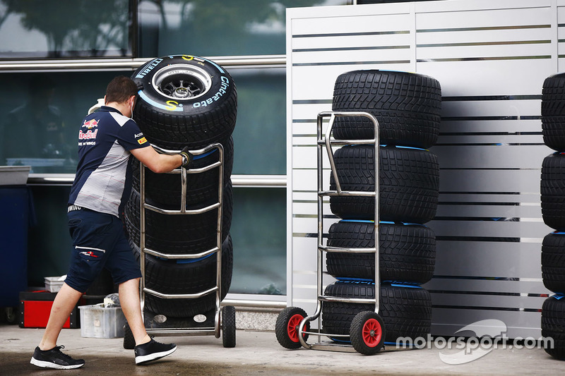 A Red Bull team member wheels a stack of Pirelli tyres