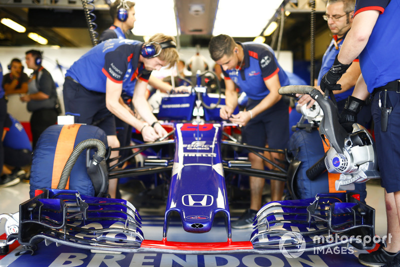 Mechanics work on the car of Brendon Hartley, Toro Rosso STR13, in the garage