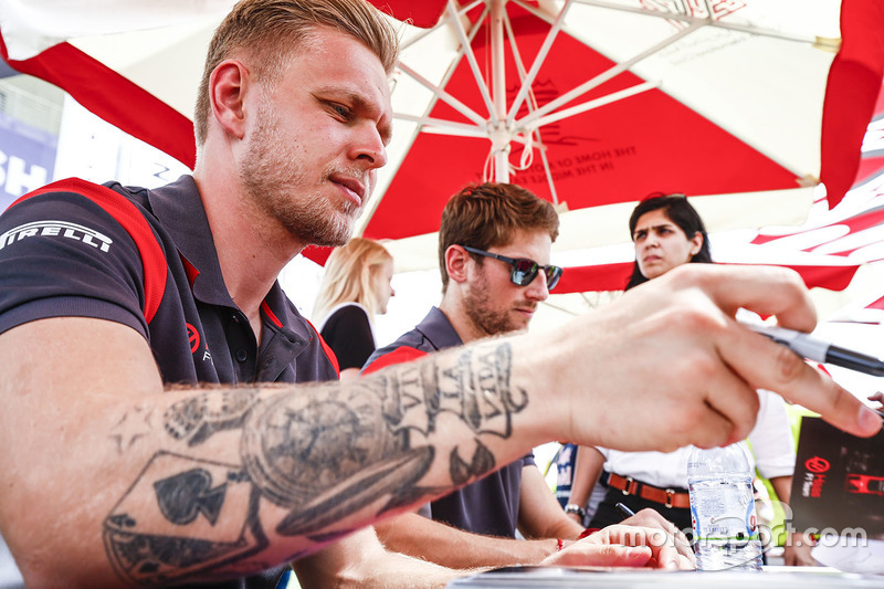 Kevin Magnussen, Haas F1 Team, and Romain Grosjean, Haas F1 Team, sign autographs for fans