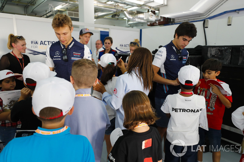 Sergey Sirotkin, Williams Racing, Lance Stroll, Williams Racing, and Brendon Hartley, Toro Rosso, sign autographs for children