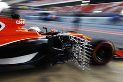Fernando Alonso, McLaren, exits his garage carrying sensor equipment