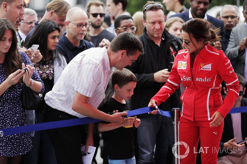 A young fan is invited under the barrier for a closer look at the activities by Ferrari promotional
