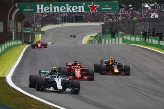 Valtteri Bottas, Mercedes AMG F1 W09, leads Sebastian Vettel, Ferrari SF71H, and a sparking Max Verstappen, Red Bull Racing RB14.
