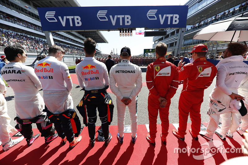 The drivers line up for the national anthem